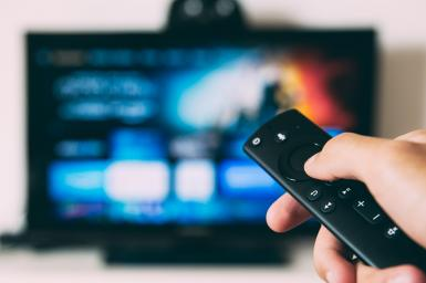 graphic of blurred TV screen and hand holding remote
